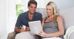 Beautiful pregnant couple shopping for baby supplies from home Stock Photography