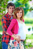 Beautiful pregnant couple in spring garden Royalty Free Stock Images