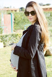 Beautiful pregnant female model with sun glasses smiling at camera Royalty Free Stock Images