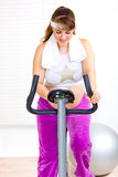 Beautiful pregnant female training on bike at home Royalty Free Stock Image