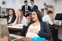 Beautiful pregnant girl eats apple. Adult pregnant girl caress pregnant belly. Pregnant women in office. Pregnancy in work Royalty Free Stock Image