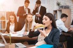 Beautiful pregnant girl eats sandwich. Adult pregnant girl caress pregnant belly. Pregnant women in office. Pregnancy in work Royalty Free Stock Image
