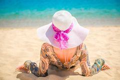Beautiful pregnant girl in hat at sea background. A Beautiful pregnant girl in hat at sea background stock photos