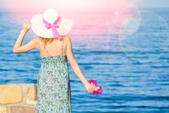 Beautiful pregnant girl in hat at sea background. A Beautiful pregnant girl in hat at sea background royalty free stock image