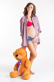 Beautiful pregnant girl is holding big toy bear Royalty Free Stock Image