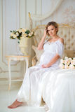Beautiful pregnant girl in a home clothes sitting in the interior on a bed of roses Stock Image