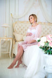 Beautiful pregnant girl in a home clothes sitting in the interior on a bed of roses Royalty Free Stock Photos