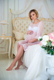 Beautiful pregnant girl in a home clothes sitting in the interior on a bed of roses Stock Photography