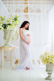 Beautiful pregnant girl in interior with flowers and tulle curtains Royalty Free Stock Photos