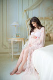 Beautiful pregnant girl in a lace negligee sitting on a bed of roses Royalty Free Stock Photo