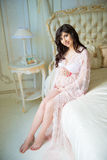 Beautiful pregnant girl in a lace negligee sitting on a bed of roses Royalty Free Stock Photos