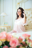 Beautiful pregnant girl in a lace negligee sitting on a bed of roses and touching hair. Royalty Free Stock Images
