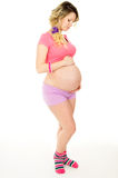 Beautiful pregnant girl looking at belly isolated Stock Photography