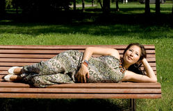 Beautiful pregnant girl lying on bench Stock Photography