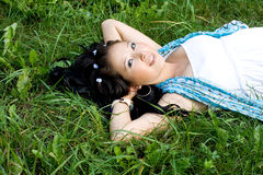 Beautiful pregnant girl lying on grass Royalty Free Stock Images