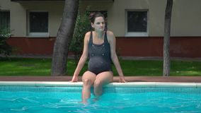 A beautiful pregnant girl with one-piece bathing suit sitting near the pool. stock video footage
