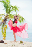 Beautiful pregnant girl in red  dress on sandy beach with palm trees Royalty Free Stock Photo