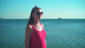 A pregnant girl in a red one-piece swimsuit and glasses is standing on the shores of the sea and smiling at the camera. A beautiful pregnant girl in a red one stock footage