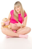 Beautiful pregnant girl sits with a toy bear Stock Photography