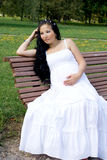 Beautiful pregnant girl sitting on bench Royalty Free Stock Photos