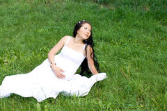 Beautiful pregnant girl sitting on grass Stock Photography