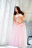 Beautiful pregnant girl standing near a window in a tulle skirt. Royalty Free Stock Photos