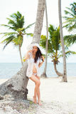 Beautiful pregnant girl in white dress and wide-brimmed hat on beach near palm trees Royalty Free Stock Photography
