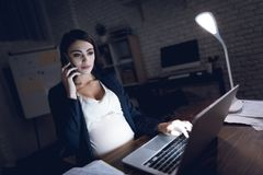 Beautiful young pregnant girl working on laptop. Pregnant in dark office. Beautiful pregnant girl working on laptop. Pregnant in dark office. Pretty pregnant Stock Photography