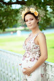 Beautiful pregnant girl with a wreath of flowers Stock Image