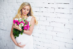 Beautiful pregnant lady with a bouquet of flowers waiting for the baby. Pregnancy. Royalty Free Stock Photo