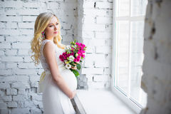 Beautiful pregnant lady with a bouquet of flowers waiting for the baby. Pregnancy. Stock Photo
