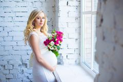 Beautiful pregnant lady with a bouquet of flowers waiting for the baby. Pregnancy. Royalty Free Stock Image
