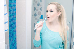 Beautiful pregnant lady having fun. Blonde holding her toothbrush and singing a song. Indoor shot Royalty Free Stock Photo