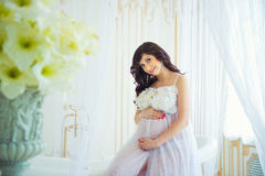 Beautiful pregnant in light white dress with orchids Royalty Free Stock Photo