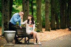 Beautiful pregnant stylish couple relaxing outside in the autumn park sitting on bench. Stock Photography