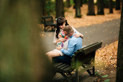 Beautiful pregnant stylish couple relaxing outside in the autumn park sitting on bench. Stock Images