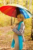 Beautiful pregnant woman in autumn forest. Under rainbow colorful umbrella Royalty Free Stock Photos
