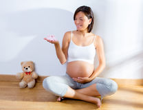 Beautiful pregnant woman with baby shoes on hand Royalty Free Stock Photography