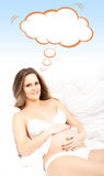 Beautiful pregnant woman in bed with conceptual cloud Royalty Free Stock Images