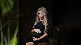Beautiful pregnant woman in black dress sitting staring on her left and touching her belly lovingly in the dark room on. The big brown leather sofa with the stock footage
