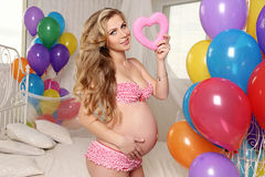 Beautiful pregnant woman with blond hair posing with colorful air ballons and decorate heart,symbol of Valentine's day Royalty Free Stock Image
