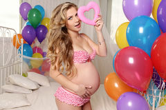 Beautiful pregnant woman with blond hair posing with colorful air ballons and decorate heart,symbol of Valentine's day Stock Images