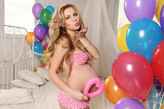 Beautiful pregnant woman with blond hair posing with colorful air ballons and decorate heart,symbol of Valentine's day Royalty Free Stock Photos
