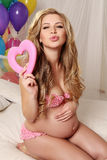 Beautiful pregnant woman with blond hair posing with colorful air ballons and decorate heart,symbol of Valentine's day Stock Photo