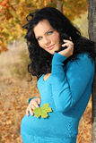 Beautiful pregnant woman in blue jacket relaxing Stock Photo