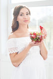 Beautiful pregnant woman with a bowl of strawberries Stock Photos