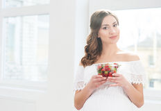 Beautiful pregnant woman with a bowl of strawberries Stock Photo