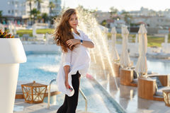Beautiful pregnant woman with chic hair smiling in a white shirt Stock Images