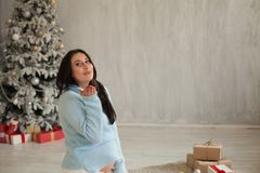 Beautiful pregnant woman childbirth on Christmas New Year holiday gifts. Beautiful pregnant woman childbirth on Christmas New Year gifts royalty free stock photography
