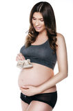 Beautiful pregnant woman with childhood her shoes Stock Image